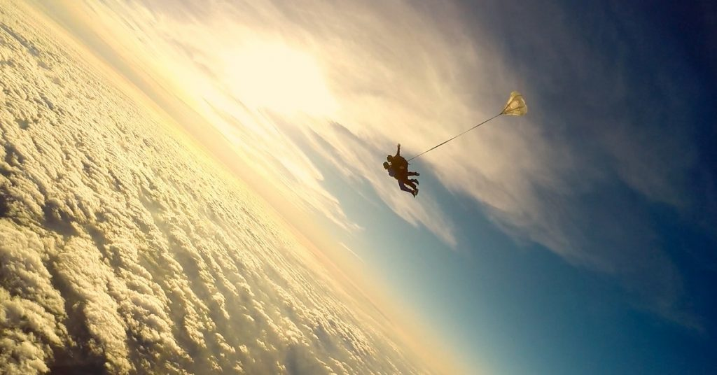 A sillhouette of 2 people tandem skydiving
